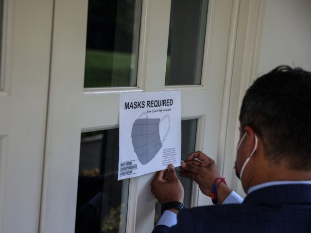 WASHINGTON, DC - JULY 27: Fin Gomez, a journalist with CBS News and White House Correspondents Association (WHCA) board member, replaces signs for mask-wearing guidance around the James Brady Press Briefing Room at the White House on July 27, 2021 in Washington, DC. The White House announced it was reimposing …
