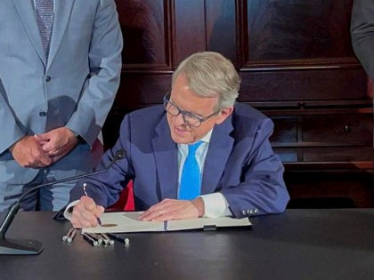 Ohio Governor Mike DeWine signs an executive order allowing college athletes in Ohio to earn money off their name, image and likeness Monday, June 28, 2021, at the Ohio Statehouse in Columbus, Ohio. The order would bring Ohio up to speed with more than a dozen states who now prevent …