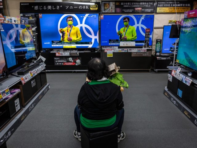 TOKYO, JAPAN - JULY 29: A woman watches Olympics games on televisions at an electronics retail store on July 29, 2021 in Tokyo, Japan. Fans have been barred from most Olympic events due to the Covid-19 pandemic, which also caused the Games' yearlong postponement. (Photo by Yuichi Yamazaki/Getty Images)