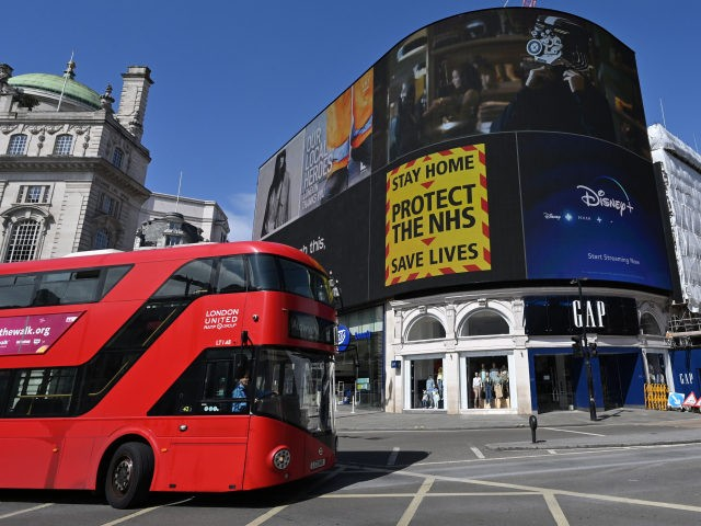 """A government sign advising people to """"Stay Home, Protect the NHS, Save Lives"""" is displayed on the advertising boards in Piccadilly Circus in the spring sunshine on the bank holiday Monday in London on April 13, 2020, as life in Britain continues over the Easter weekend, during the nationwide lockdown …"""