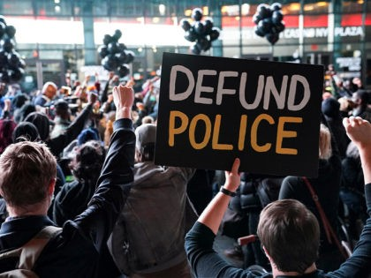 """FILE - In this Oct. 14, 2020, file photo a protester holds a sign that reads """"Defund Police"""" during a rally for the late George Floyd outside Barclays Center in New York. Some police organizations and Republican politicians are blaming Democrats and last year's defund the police effort for a …"""