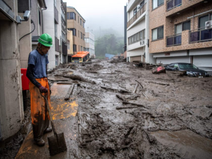 A rescue worker removes mud and debris at the scene of a landslide following days of heavy rain in Atami in Shizuoka Prefecture on July 3, 2021. (Photo by Charly TRIBALLEAU / AFP) (Photo by CHARLY TRIBALLEAU/AFP via Getty Images)
