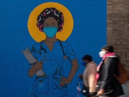People walk past a mural by artist M. Tony Peralta picturing a healthcare worker at New York Presbyterian Hospital on March 22, 2021 in New York City. - RESTRICTED TO EDITORIAL USE - MANDATORY MENTION OF THE ARTIST UPON PUBLICATION - TO ILLUSTRATE THE EVENT AS SPECIFIED IN THE CAPTION …