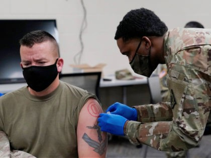 Maj. Michael Childress receives a bandage from Sgt. Christian Minor after being inoculated with the Moderna COVID-19 vaccine at the Mississippi National Guard's 172d Airlift Wing facility in Flowood, Miss., Wednesday, Dec. 23, 2020. One hundred doses of the vaccine were administered to both Mississippi Air and Army National Guard …
