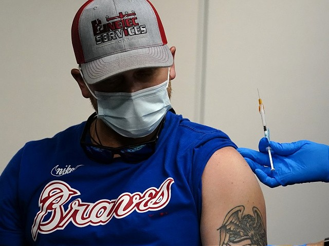 Atlanta Braves fan Reid Bonner gets a COVID-19 vaccine before a baseball game between the Braves and the Philadelphia Phillies, Friday, May 7, 2021, in Atlanta. The Braves were offering free tickets to an upcoming game to fans who got the shot. (AP Photo/John Bazemore)