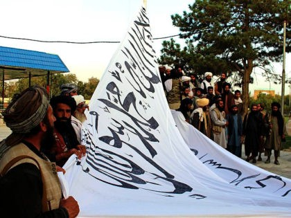 Taliban fighters raise their flag at the Ghazni provincial governor's house, in Ghazni, southeastern, Afghanistan, Sunday, Aug. 15, 2021. (AP Photo/Gulabuddin Amiri)