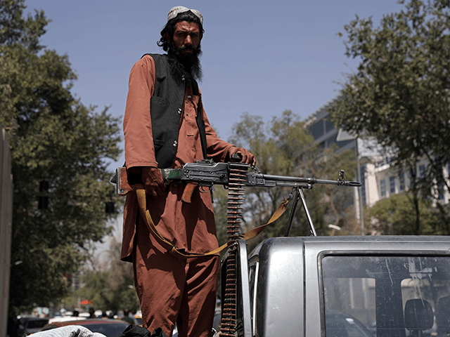 A Taliban fighter sits on the back of vehicle with a machine gun in front of the main gate leading to the Afghan presidential palace, in Kabul, Afghanistan, Monday, Aug. 16, 2021. The U.S. military has taken over Afghanistan's airspace as it struggles to manage a chaotic evacuation after the Taliban rolled into the capital. (AP Photo/Rahmat Gul)