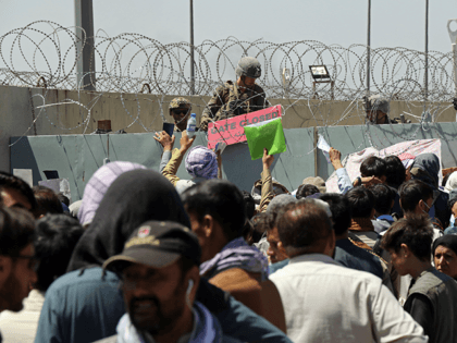 A U.S. soldier holds a sign indicating a gate is closed as hundreds of people gather some holding documents, near an evacuation control checkpoint on the perimeter of the Hamid Karzai International Airport, in Kabul, Afghanistan, Thursday, Aug. 26, 2021. Western nations warned Thursday of a possible attack on Kabul's …