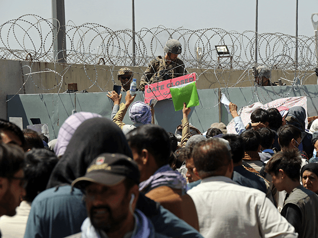 A U.S. soldier holds a sign indicating a gate is closed as hundreds of people gather some holding documents, near an evacuation control checkpoint on the perimeter of the Hamid Karzai International Airport, in Kabul, Afghanistan, Thursday, Aug. 26, 2021. Western nations warned Thursday of a possible attack on Kabul's airport, where thousands have flocked as they try to flee Taliban-controlled Afghanistan in the waning days of a massive airlift. Britain said an attack could come within hours. (AP Photo/Wali Sabawoon)