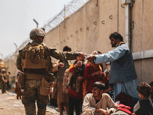 HAMID KARZAI INTERNATIONAL AIRPORT, AFGHANISTAN - AUGUST 22: This handout image shows A Marine with the 24th Marine Expeditionary unit (MEU) passes out water to evacuees during an evacuation at Hamid Karzai International Airport, Kabul, Afghanistan, Aug. 22. U.S. service members are assisting the Department of State with a Non-combatant …