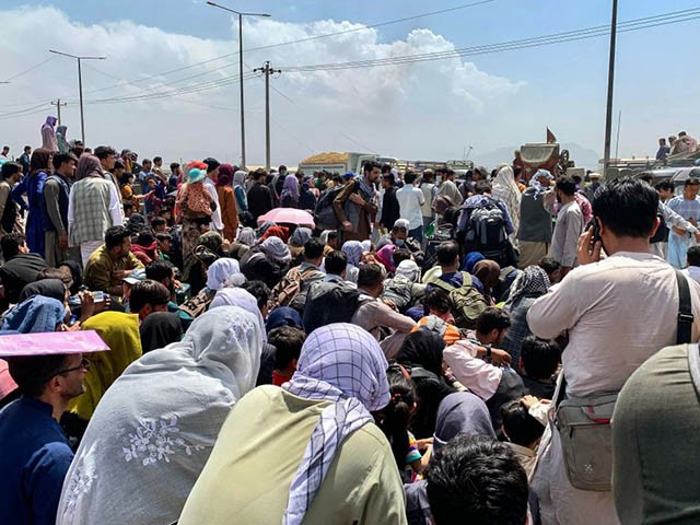 Afghan people gather along a road as they wait to board a U S military aircraft to leave the country, at a military airport in Kabul on August 20, 2021 days after Taliban's military takeover of Afghanistan. (Photo by Wakil KOHSAR / AFP) (Photo by WAKIL KOHSAR/AFP via Getty Images)