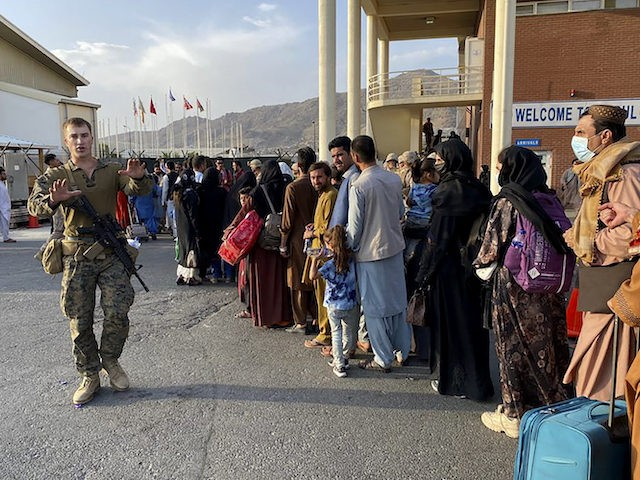 Afghan people queue up to board a U S military aircraft to leave Afghanistan, at the military airport in Kabul on August 19, 2021 after Taliban's military takeover of Afghanistan. (Photo by Shakib RAHMANI / AFP) (Photo by SHAKIB RAHMANI/AFP via Getty Images)