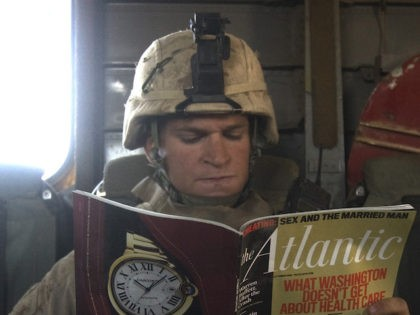 A US Marine reads a copy of Atlantic magazine with a cover photo of US President Barack Obama as he rides on a CH-53 helicopter flying over Helmand Province, southern Afghanistan, on October 12, 2009. Twenty Taliban militants were killed and a number arrested in separate operations involving foreign forces …