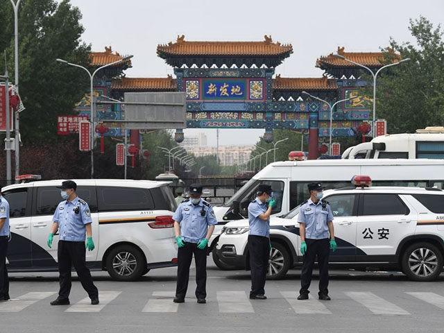 TOPSHOT - Chinese police guard the entrance to the closed Xinfadi market in Beijing on June 13, 2020. - Eleven residential estates in south Beijing have been locked down due to a fresh cluster of coronavirus cases linked to the Xinfadi meat market, officials said on June 13. (Photo by …