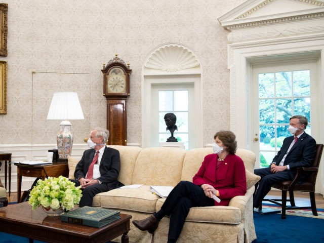 Senator Angus S. King Jr. (I-ME), Senator Jeanne Shaheen (D-NH), and Senator John Hickenlooper (D-CO) listens while US President Joe Biden(L) speaks before a meeting about the American Jobs Plan in the Oval Office of the White House April 19, 2021, in Washington, DC. (Photo by Brendan Smialowski / AFP) …