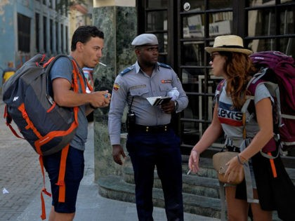 """A policeman guides tourists in Havana on March 24, 2020 during the global coronavirus COVID-19 pandemic. - From Tuesday, Cuba -- which has so far counted 40 cases of the new coronavirus, which the government says have all been """"imported"""" -- will close its borders to tourists for a month …"""