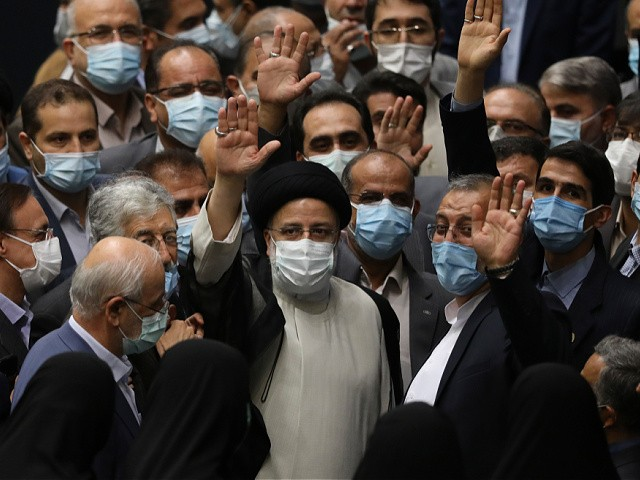 President Ebrahim Raisi, center, waves to journalists as he is surrounded by group of lawmakers after taking his oath as president at the parliament in Tehran, Iran, Thursday, Aug. 5, 2021. The inauguration of Raisi, a protégé of Iran's supreme leader, completes hard-liners' dominance of all branches of government in the Islamic Republic. (AP Photo/Vahid Salemi)