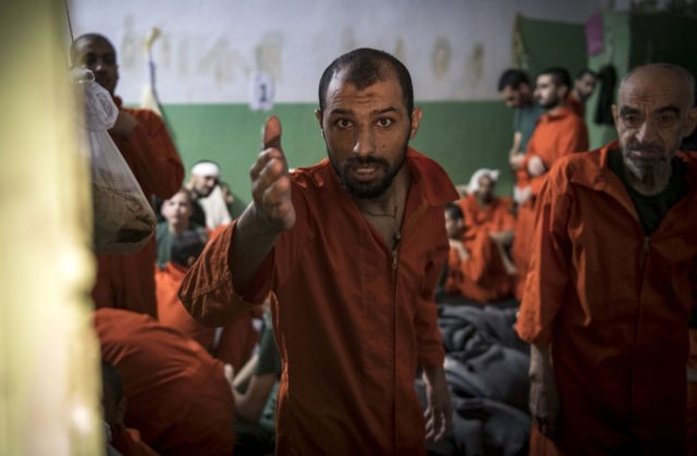 TOPSHOT - Men, suspected of being affiliated with the Islamic State (IS) group, gather in a prison cell in the northeastern Syrian city of Hasakeh on October 26, 2019. - Kurdish sources say around 12,000 IS fighters including Syrians, Iraqis as well as foreigners from 54 countries are being held …