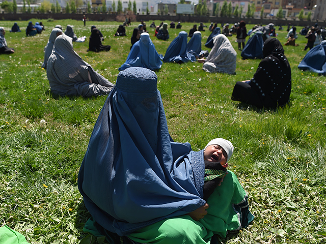 A woman wearing a burqa holds her child as she waits to receive free wheat from the government emergency committee during a government-imposed lockdown on the capital city as a preventive measure against the COVID-19 coronavirus, in Kabul on April 21, 2020. (Photo by WAKIL KOHSAR / AFP) (Photo by WAKIL KOHSAR/AFP via Getty Images)