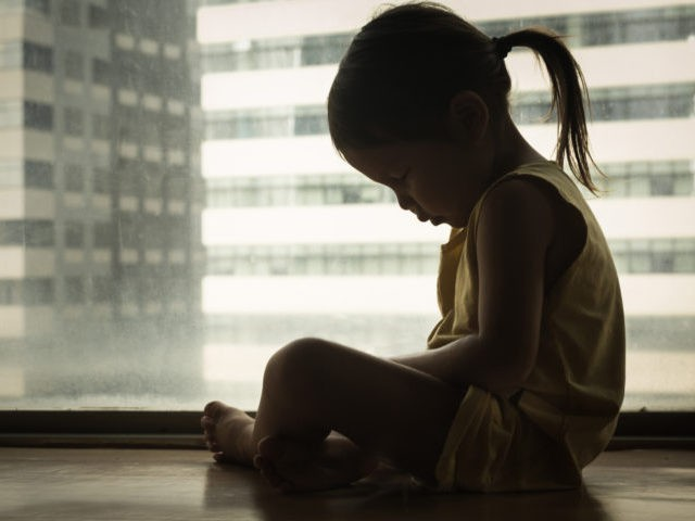 A litte girl sitting next to a window with her head down in sadness. Feeling depressed and hurt.