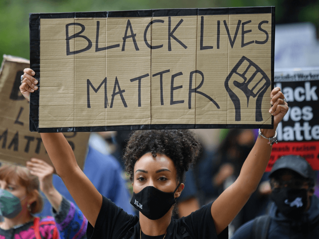 """People hold up placards in support of the Black Lives Matter movement as they take part in the inaugural Million People March march from Notting Hill to Hyde Park in London on August 30, 2020, to put pressure on the UK Government into changing the """"UK's institutional and systemic racism"""". - The march is organised by The Million People Movement, and takes place on the bank holiday weekend usually associated with the Notting Hill Carnival, this year cancelled due to the coronavirus covid-19 pandemic. (Photo by JUSTIN TALLIS / AFP) (Photo by JUSTIN TALLIS/AFP via Getty Images)"""