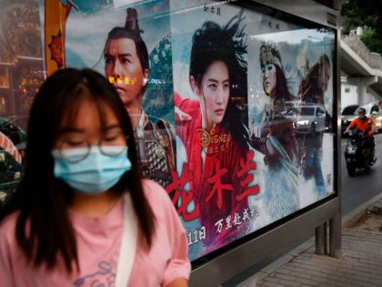 """A woman waits beside a poster for the Disney movie """"Mulan"""" at a bus stop on the day the movie opened in Beijing on September 11, 2020. - Pilloried internationally and given a lukewarm debut by Chinese cinemagoers, Disney on September 11 discovered its $200 million live-action epic """"Mulan"""" has …"""