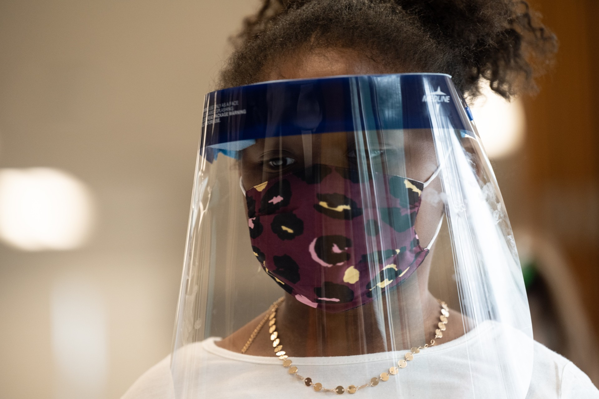LOUISVILLE, KY - MARCH 17: A child wearing a face shield and mask stands in the cafeteria of Medora Elementary School on March 17, 2021 in Louisville, Kentucky. Today marks the reopening of Jefferson County Public Schools for in-person learning with new COVID-19 procedures in place. (Photo by Jon Cherry/Getty Images)