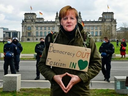 A protestor wearing a mask depicting German Chancellor Angela Merkel takes part in a demonstration in Berlin on April, 13, 2021, as anti lockdown critics and so-called 'Querdenker' gathered outside the German parliament on Tuesday, amid the Covid-19, corona pandemic. (Photo by John MACDOUGALL / AFP) (Photo by JOHN MACDOUGALL/AFP …