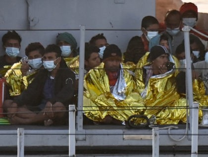 Migrants warmed by emergency blankets arrive on a boat of the Italian Guardia Di Finanza law enforcement agency on May 17, 2021 to disembark on the southern Italian Pelagie Island of Lampedusa. - More than 1,400 migrants arrived on the Italian island of Lampedusa at the weekend, sparking calls from …