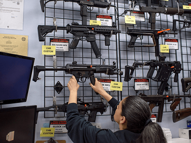 Employee Gorety Mejia takes down a HK MP5 for a customer at Full Armor Firearms store in Houston, Texas on June 17, 2021. - Governor Greg Abbott signed into law Wednesday a bill that allows Texans to carry firearms in public without a permit, the latest in a series of …