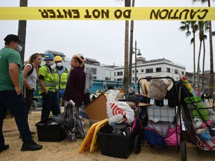 Dixie Moore (R) talks with representatives from St Joseph Center Homeless Services who will help her move from her tent encampment along the Venice Beach Boardwalk, to short-term housing in a nearby hotel July 2, 2021 in Los Angeles, California, as city sanitation workers prepare to clear the area ahead …