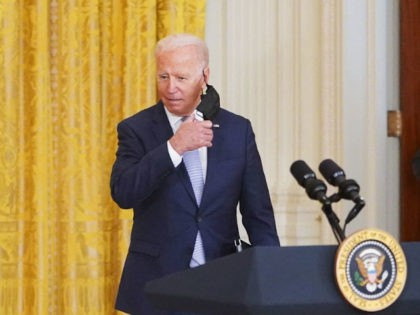 US President Joe Biden takes off his mask as he arrivers to speak on prescription drug prices in the East Room of the White House in Washington, DC on August 12, 2021. (Photo by MANDEL NGAN / AFP) (Photo by MANDEL NGAN/AFP via Getty Images)