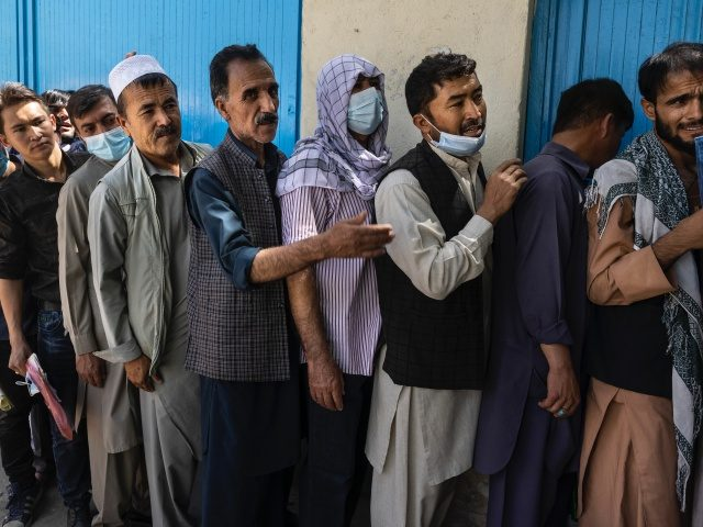 Afghans wait in long lines for hours at the passport office as many are desperate to have their travel documents ready to go on August 14, 2021 in Kabul, Afghanistan. (Paula Bronstein /Getty Images)