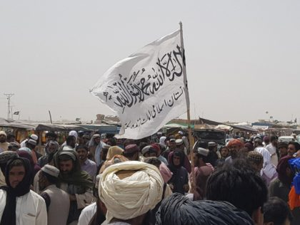 TOPSHOT - People gather around a Taliban flag as they wait for relatives released from jail in Afghanistan following an 'amnesty' by the Taliban, near the Pakistan-Afghanistan border crossing point in Chaman on August 17, 2021. (Photo by - / AFP) (Photo by -/AFP via Getty Images)