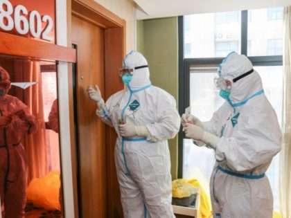 Medical staff members wearing personal protective equipment (PPE) against the spread of Covid-19 coronavirus knock on a door as they collect samples to be tested for the virus at a quarantine hotel in Lianyungang in China's eastern Jiangsu province on August 19, 2021. - China OUT (Photo by STR / …