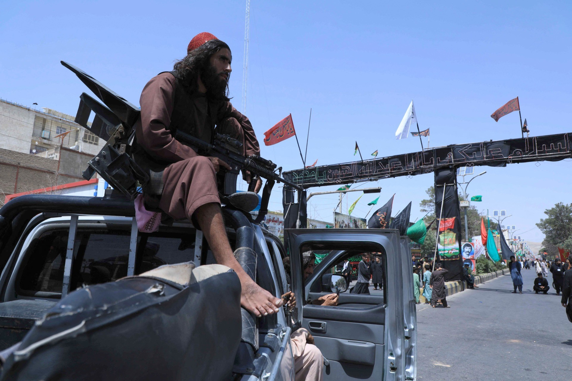 A Taliban fighter stands guard atop a vehicle near the site of an Ashura procession which is held to mark the death of Imam Hussein, the grandson of Prophet Mohammad, along a road in Herat on August 19, 2021, amid the Taliban's military takeover of Afghanistan. (Photo by AREF KARIMI / AFP) (Photo by AREF KARIMI/AFP via Getty Images)