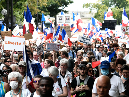 """Protesters wave French flags and hold banners reading """"freedom"""" as they march during a national day of protest against the compulsory Covid-19 vaccination for certain workers and the mandatory use of the health pass called for by the French government in Paris on August 21, 2021. - Protesters took to …"""