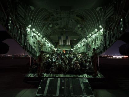 KABUL, AFGHANISTAN - AUGUST 21: In this handout provided by the U.S. Air Force, an air crew assigned to the 816th Expeditionary Airlift Squadron assists evacuees aboard a C-17 Globemaster III aircraft in support of the Afghanistan evacuation at Hamid Karzai International Airport on August 21, 2021 in Kabul, Afghanistan. …