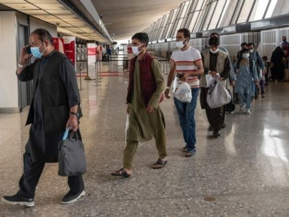Refugees from Afghanistan are escorted to a waiting bus after arriving and being processed at Dulles International Airport in Dulles, Virginia on August 23, 2021. - Around 16,000 people were evacuated over the past 24 hours from Afghanistan through the Kabul airport, the Pentagon said on August 23, 2021, as …