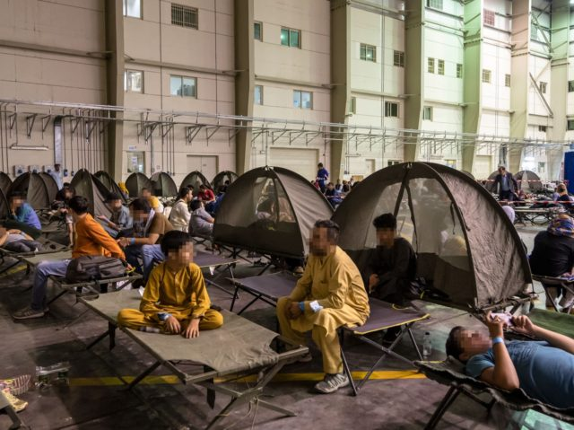 """Refugees wait at an evacuation centre after they left Kabul as part of the operation """"Apagan"""" at the French military air base 104 of Al Dhafra, near Abu Dhabi, on August 23, 2021. - - EDITORS NOTE : Some faces have been pixelated at the request of French Defence Ministry …"""