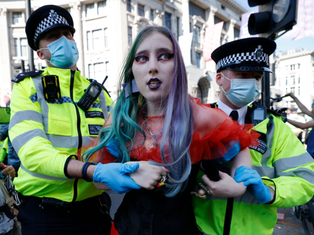 Police officers take away a climate activist from the Extinction Rebellion group during the group's 'Impossible Rebellion' series of actions at Oxford Circus in central London, on August 25, 2021. - Climate change demonstrators from environmental activist group Extinction Rebellion continued with their latest round of protests in central London, …
