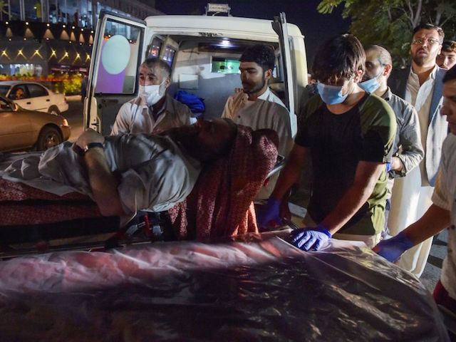 EDITORS NOTE: Graphic content / Volunteers and medical staff bring an injured man for treatment after two powerful explosions, which killed at least six people, outside the airport in Kabul on August 26, 2021. (Photo by Wakil KOHSAR / AFP) (Photo by WAKIL KOHSAR/AFP via Getty Images)