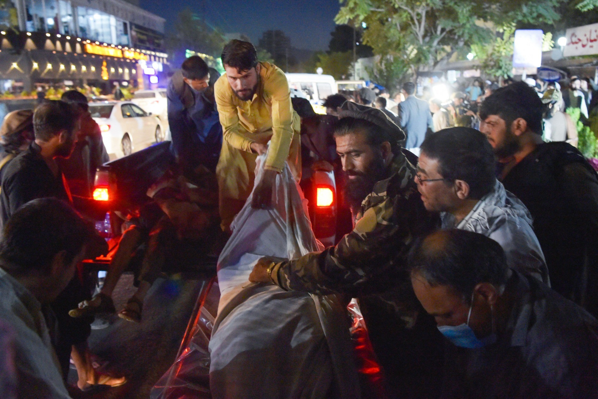EDITORS NOTE: Graphic content / TOPSHOT - Volunteers and medical staff unload bodies from a pickup truck outside a hospital after two powerful explosions, which killed at least six people, outside the airport in Kabul on August 26, 2021. (Photo by Wakil KOHSAR / AFP) (Photo by WAKIL KOHSAR/AFP via Getty Images)