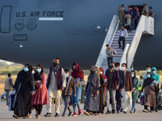 Refugees disembark from a US air force aircraft after an evacuation flight from Kabul at the Rota naval base in Rota, southern Spain, on August 31, 2021. - Spain has agreed to host up to 4,000 Afghans who will be airlifted by the United States to airbases in Rota and …
