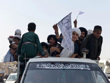 TOPSHOT - Youths supporting the Taliban wave Taliban flags atop a vehicle while marching with others along a street in Kandahar on August 31, 2021, as they celebrate after the US has pulled all its troops out of the country to end a brutal 20-year war -- one that started …