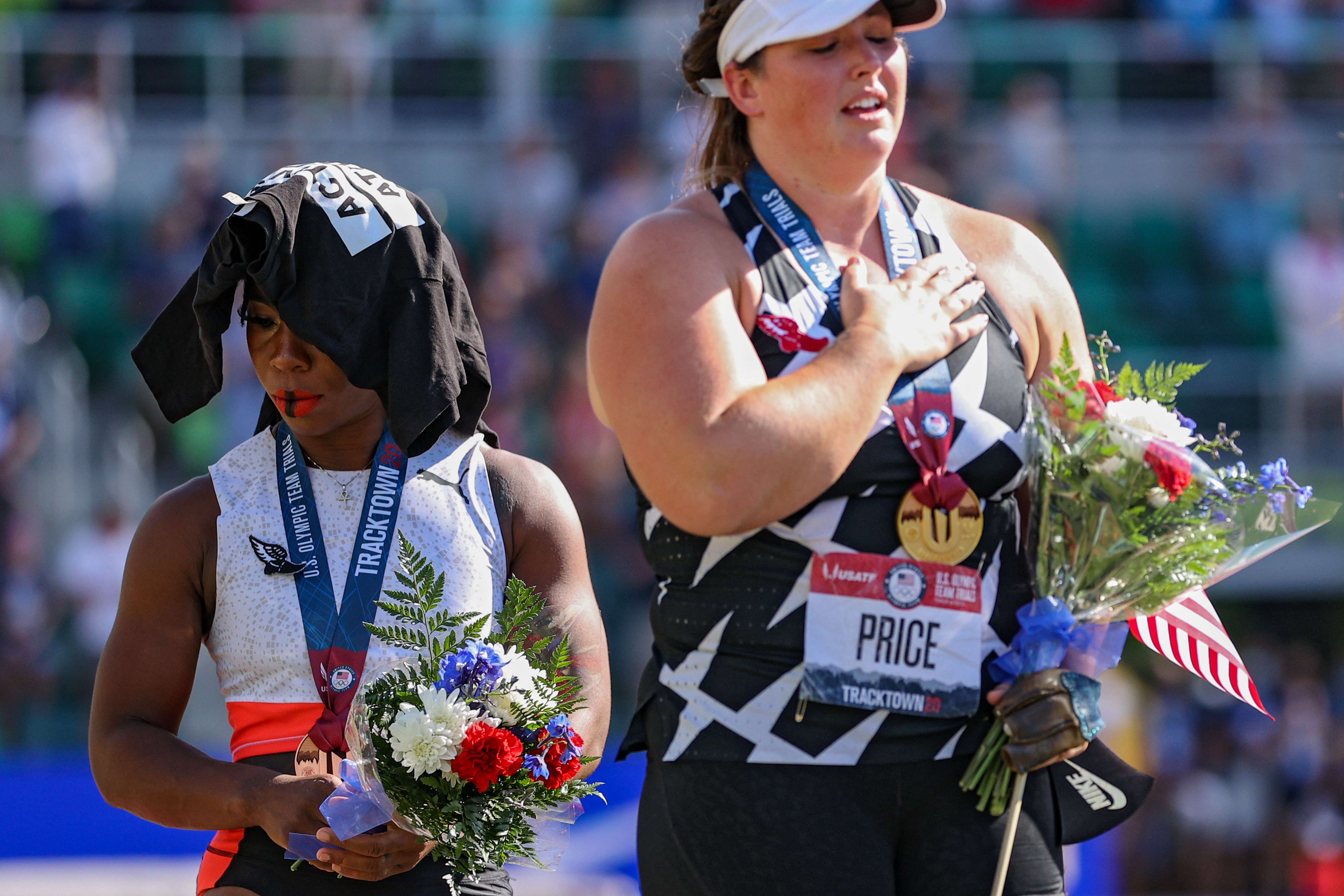 EUGENE, OREGON - JUNE 26: Gwendolyn Berry (L), third place, turns away from U.S. flag during the U.S. National Anthem as DeAnna Price (C), first place, also stands on the podium after the Women's Hammer Throw final on day nine of the 2020 U.S. Olympic Track & Field Team Trials at Hayward Field on June 26, 2021 in Eugene, Oregon. In 2019, the USOPC reprimanded Berry after her demonstration on the podium at the Lima Pan-American Games. (Photo by Patrick Smith/Getty Images)