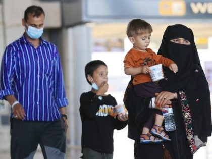 DULLES, VIRGINIA - AUGUST 27: Refugees arrive at Dulles International Airport after being evacuated from Kabul following the Taliban takeover of Afghanistan August 27, 2021 in Dulles, Virginia. Refugees continued to arrive in the United States one day after twin suicide bombings at the gates of the airport in Kabul …