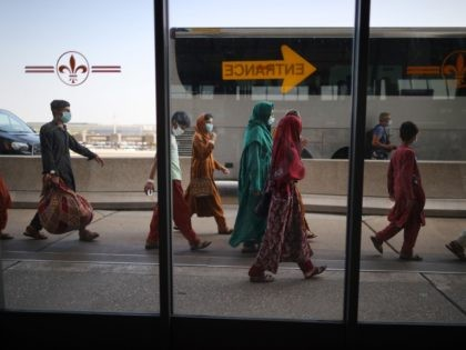 DULLES, VIRGINIA - AUGUST 27: Refugees board buses that will take them to a processing center after they arrive at Dulles International Airport after being evacuated from Kabul following the Taliban takeover of Afghanistan August 27, 2021 in Dulles, Virginia. Refugees continued to arrive in the United States one day …