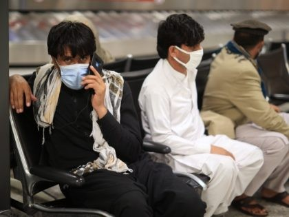 DULLES, VIRGINIA - AUGUST 27: Refugees wait for transportation at Dulles International Airport after being evacuated from Kabul following the Taliban takeover of Afghanistan August 27, 2021 in Dulles, Virginia. Refugees continued to arrive in the United States one day after twin suicide bombings at the gates of the airport …