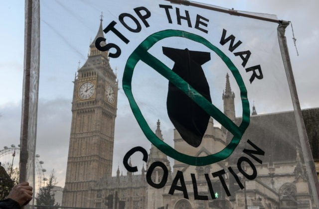 LONDON, ENGLAND - DECEMBER 02: Stop the War Coalition supporters hold up a banner outside the Houses of Parliament on December 2, 2015 in London, England. A day long debate on whether Britain should become involved with airstrikes targetting Islamic State targets in Syria will end in a vote at …